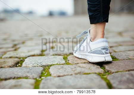 Leg Of Female Jogger Walking On Pavement