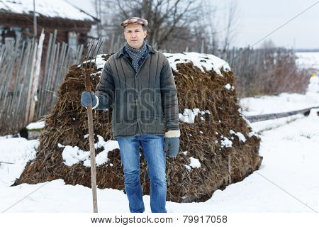 man with fork in  heap of manure