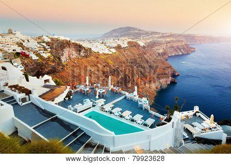 Fira, the capital of Santorini island, Greece at sunset. Swimming pool over Caldera, Aegean sea.