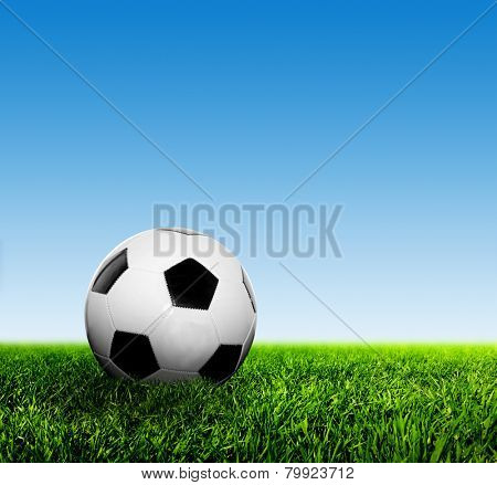 Ball on grass against blue clear sky. Football, soccer.
