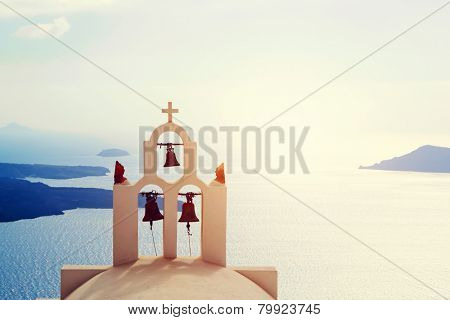 Oia town on Santorini island, Greece. Traditional bells and cross over the Caldera, Aegean sea