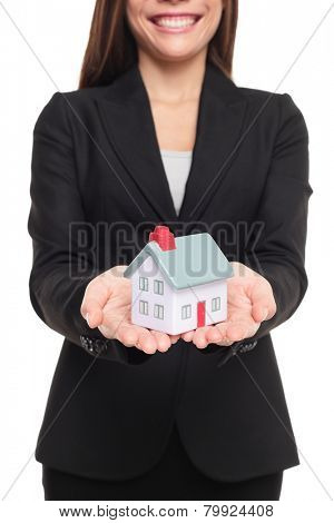 Real estate agent showing new house in mini size. New home owner concept. Realtor showing holding house model. Buying new home conceptual image with business woman in suit isolated on white background