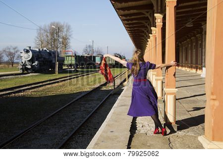 Woman In Lilac Dress And Station Pillar
