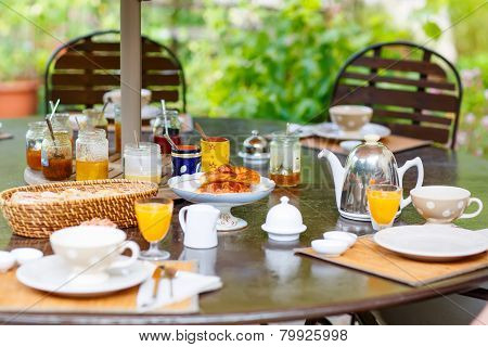 Table Laid For Breakfast Outside With Various Jams Coffee, Croissants, And Orange Juice