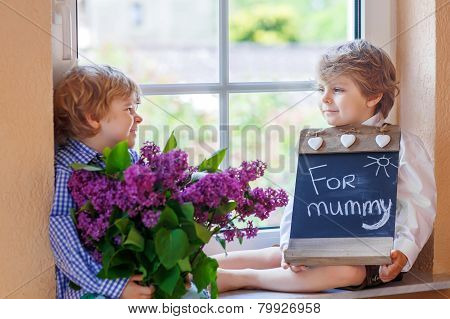 Two Adorable Little Sibling Boys With Blooming Lilac Flowers