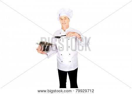 Experienced chef in white uniform mixing his soup