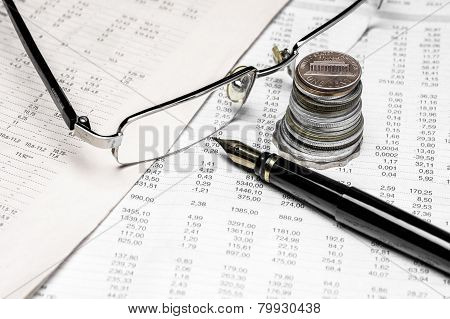 Coins, spectacles and fountain pen on a data table