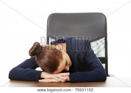 Overworked businesswoman sleeping at the desk in office
