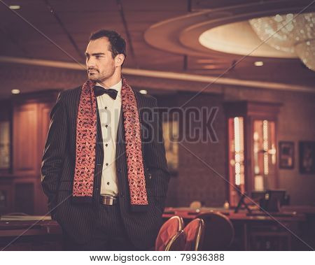 Handsome man wearing suit in luxury casino interior