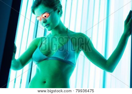 Young woman sunbathing in solarium