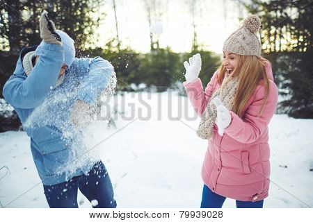 Happy young dates playing snowballs outdoors