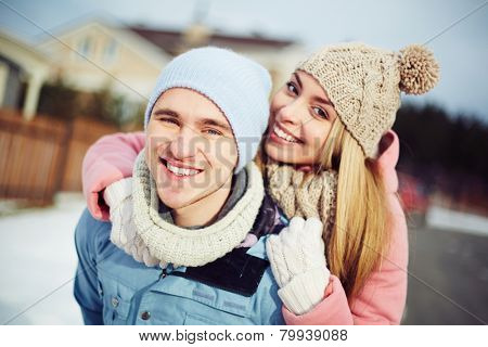 Young guy and girl in winterwear looking at camera outside