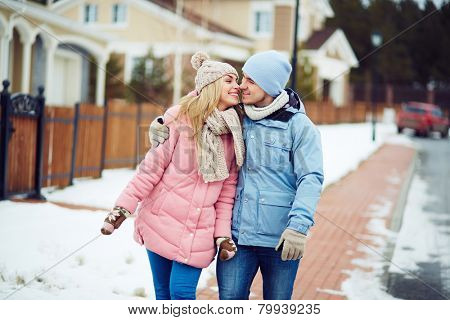 Young sweethearts walking along urban houses in winter