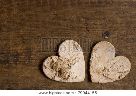 Hearts made of tree bark lying on a weathered old wooden textured table