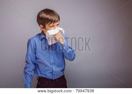 teenager boy of 10 years European appearance sick sneezing in