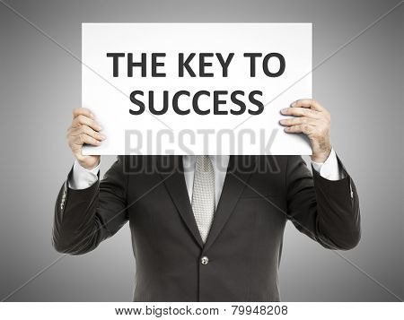 A business man holding a paper in front of his face with the message the key to success