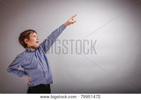 teenager boy shows his hand up on gray background