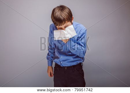 teenager boy sneezes into a handkerchief on gray background