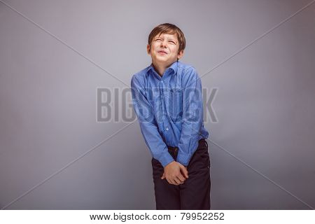 teenager boy wants to use the toilet on gray background