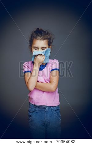 the girl child is sick in hands handkerchief on gray