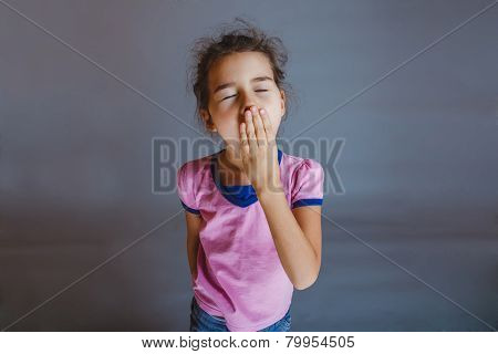 the girl child is tired closes her mouth yawns on a gray backgro