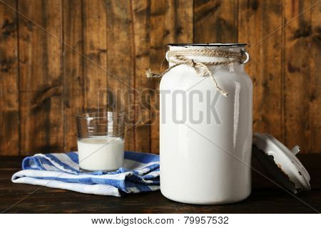 Open milk can on dishcloth on rustic wooden background