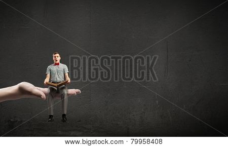 Young man student sitting with book in hands