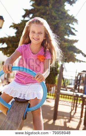 Young Girl Having Fun On Seesaw In Playground