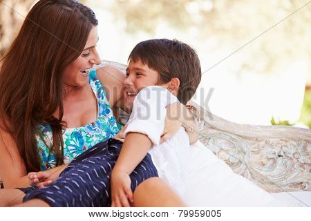 Mother At Home Sitting On Outdoor Seat And Playing With Son