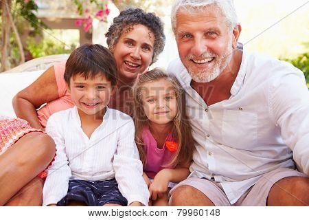 Grandparents With Grandchildren Sitting On Seat In Garden