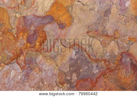 Pattern of a stone slab in rust, orange, beige, purple
