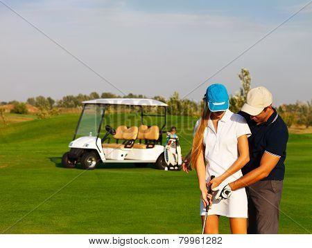 Sportive Couple Playing Golf On A Golf Course