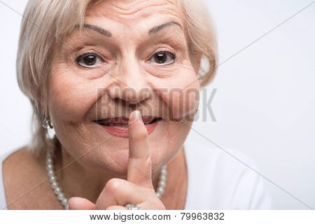 Elderly lady putting finger on her mouth