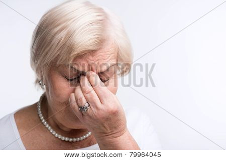 Elderly lady touching her head