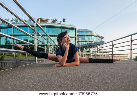 Girl sitting on the splits. Dance outdoor