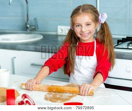 little girl unrolls dough for cookies for Valentine's Day