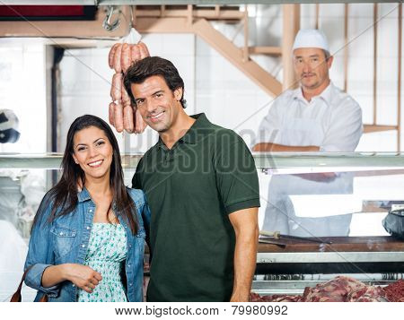 Portrait of happy mature couple standing in butcher shop