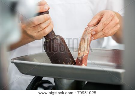 Midsection of butcher using mincing machine in butchery