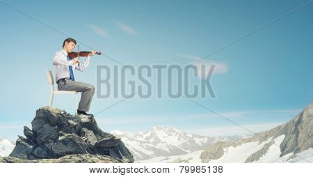 Young businessman sitting in chair and playing violin