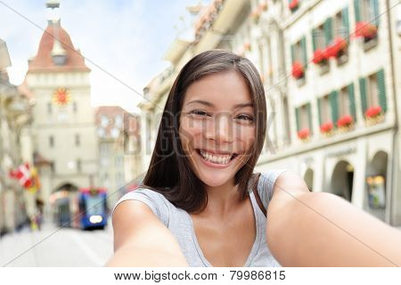 Woman taking selfie with smart phone in Bern Switzerland walking on Kramgasse, Berne main street in the old city. Young female visiting tourist attractions and landmarks.