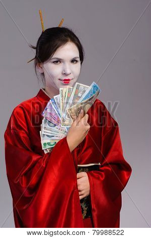 The girl in native costume of japanese geisha, isolated on grey