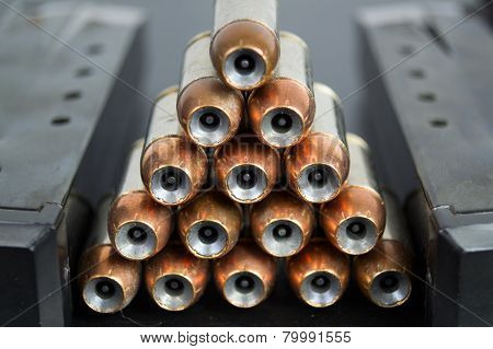 Hollow Point, Copper Jacketed Bullets Stacked In A Pyramid Between Two Magazines