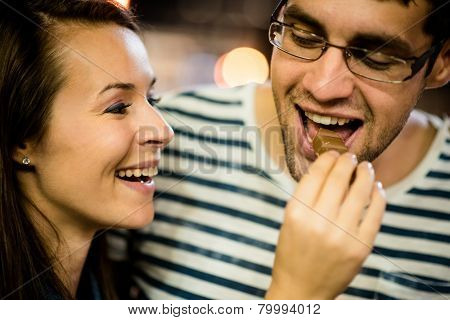Couple eating chocolate on date at night