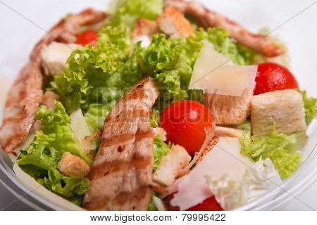 Close-up shot of delicious Caesar salad with grilled chicken meat