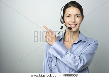 Smiling Businesswoman With A Headset Pointing