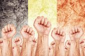 stock photo of labourer  - Belgium Labour movement workers union strike concept with male fists raised in the air fighting for their rights Belgium national flag in out of focus background - JPG