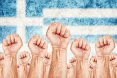 image of labourer  - Greece Labour movement workers union strike concept with male fists raised in the air fighting for their rights Greek national flag in out of focus background - JPG