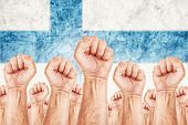 stock photo of labourer  - Finland Labour movement workers union strike concept with male fists raised in the air fighting for their rights Finnish national flag in out of focus background - JPG