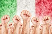 picture of labourer  - Italy Labour movement workers union strike concept with male fists raised in the air fighting for their rights Italian national flag in out of focus background - JPG