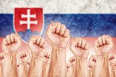 stock photo of labourer  - Slovakia Labour movement workers union strike concept with male fists raised in the air fighting for their rights Slovak national flag in out of focus background - JPG